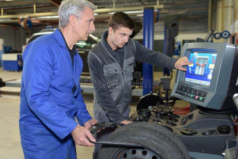 Uczeń z instruktora naprawiania samochodem podczas aplikantury obrazy royalty free