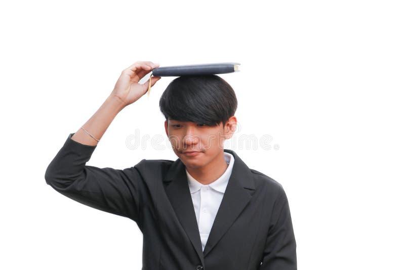 Uczeń z książką na głowie przeciw białemu tłu zdjęcie stock