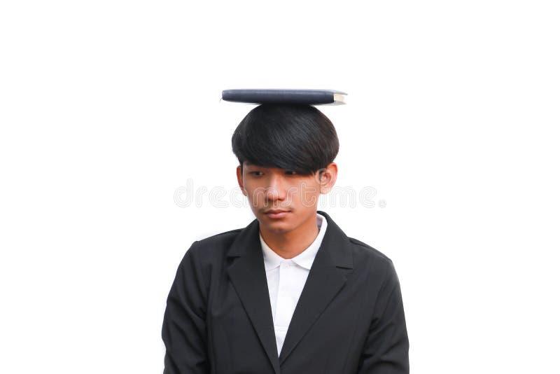 Uczeń z książką na głowie przeciw białemu tłu zdjęcia royalty free
