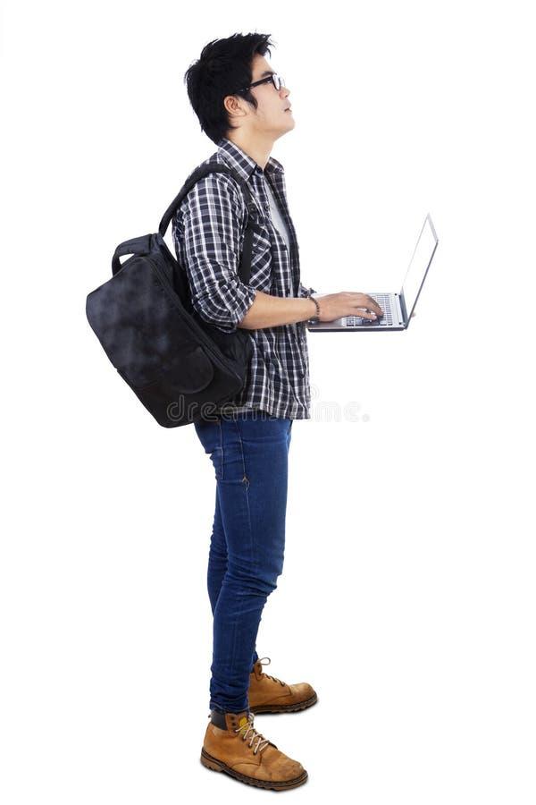 Uczeń z laptopu przyglądającym copyspace obraz stock