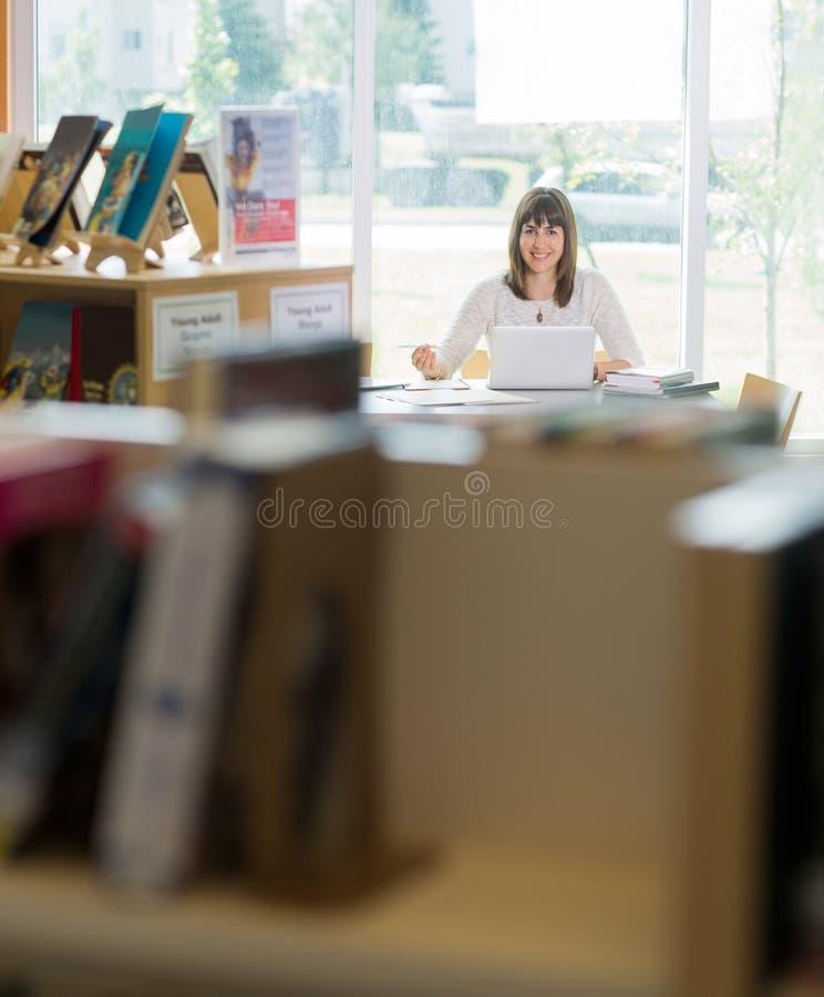 Uczeń Z laptopu studiowaniem W bibliotece zdjęcie stock