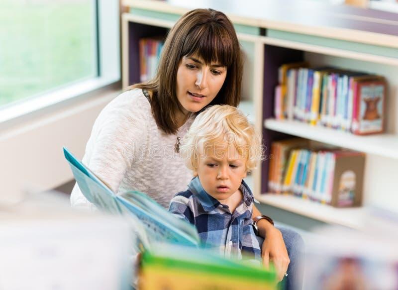 Uczeń Z nauczyciel Czytelniczą książką W bibliotece zdjęcia royalty free