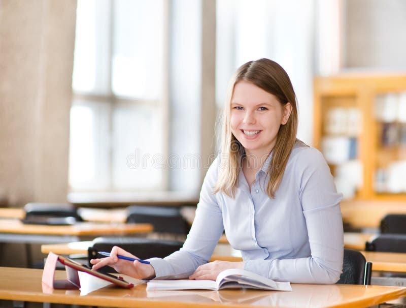 Uczeń z pastylka komputerem w bibliotece fotografia stock