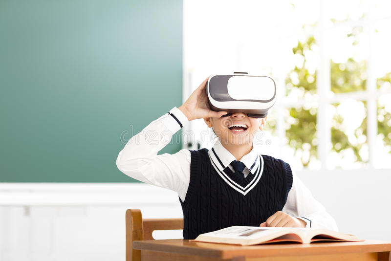 Uczeń z rzeczywistości wirtualnej słuchawki obsiadaniem w sala lekcyjnej zdjęcia royalty free