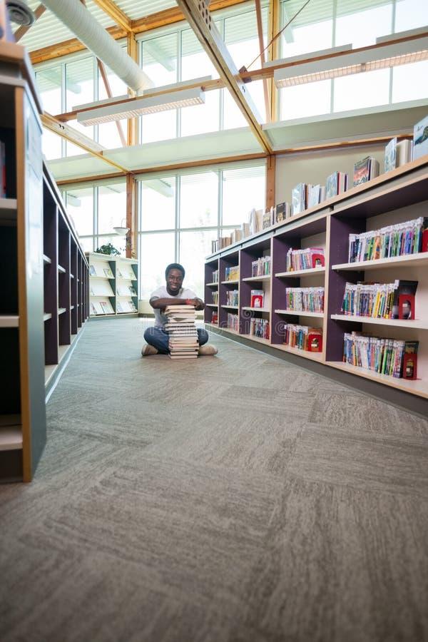 Uczeń Z stertą książki W bibliotece fotografia royalty free