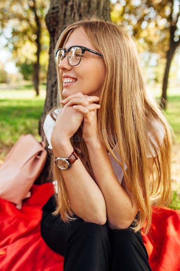 Uczeń z szkłami, odpoczywa po klasy w Parkowym obsiadaniu dalej fotografia royalty free
