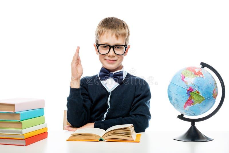 Uczeń z szkłami przy stołem z książkami i kulą ziemską ciągnie zdjęcia royalty free