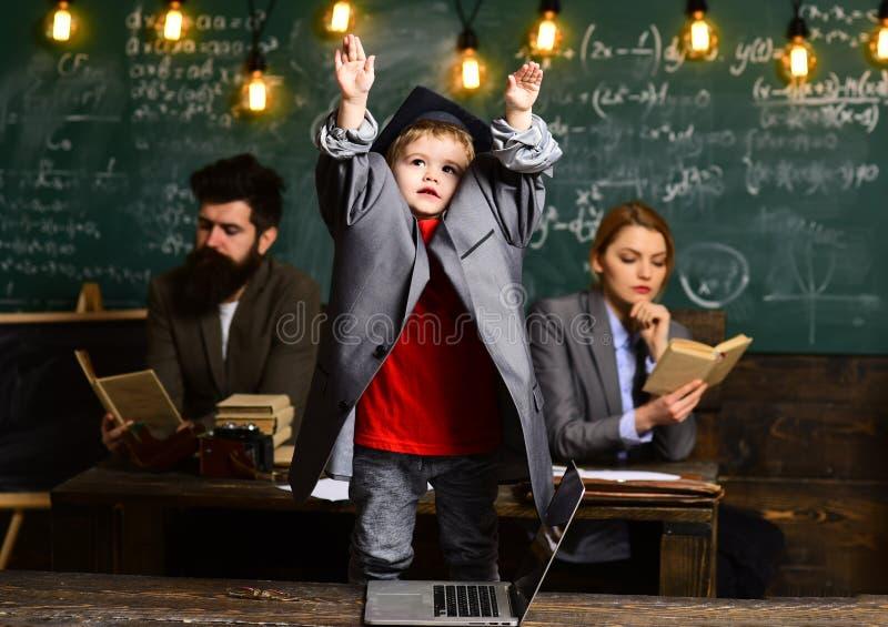 Uczeń z zamazaną matką i ojcem przy chalkboard, rodzina Uczeń chłopiec w dużym kostiumu żakiecie skalowanie nakrętce i zdjęcia royalty free