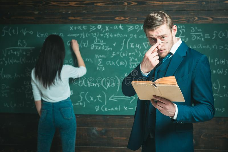 Uczenie matematyka umożliwia ja myśleć wyraźnie Nauczyciela mężczyzna w szkłach czyta problemowego oświadczenie od podręcznika dz fotografia royalty free