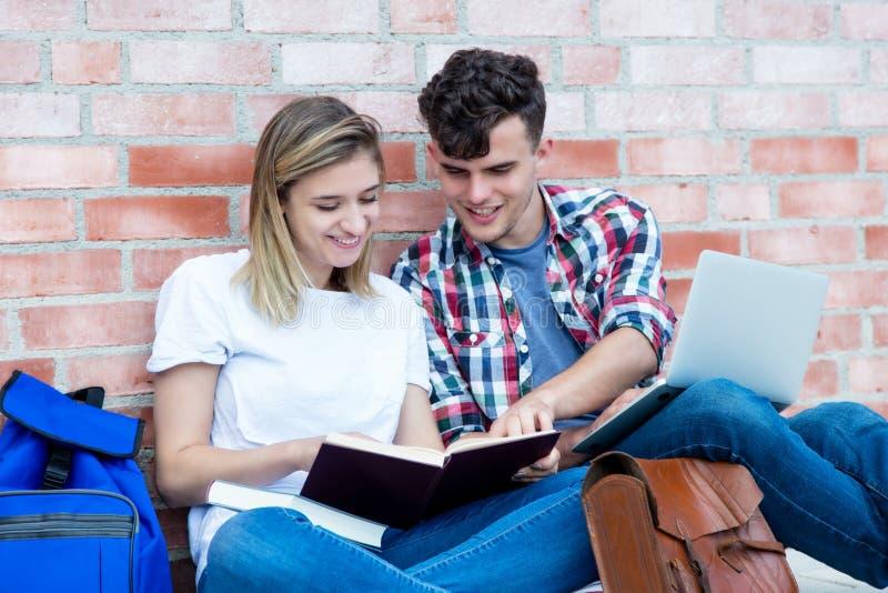 Uczenie niemieccy ucznie z książką i laptopem zdjęcia stock