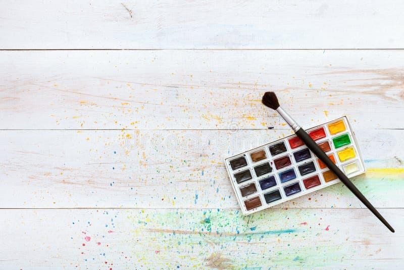 Uczenie obrazu pojęcie, farby muśnięcie i pudełko z akwarelami na białym drewnianym stole z pluśnięciami, artystyczny tło, kreaty zdjęcia stock