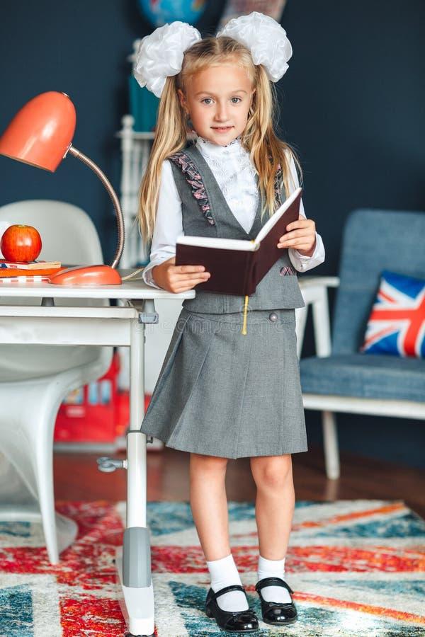 Uczennica blondy w mundurku szkolnym z bielem kłania się pozycję blisko studiowania i stołu w domu Edukacja i szko?y poj?cie obrazy stock