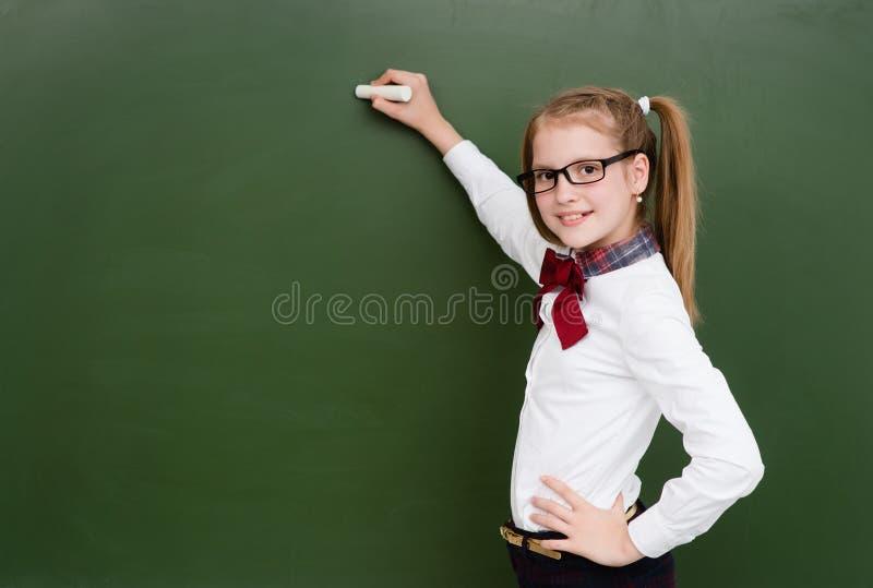 Uczennica chce pisać coś na chalkboard fotografia stock