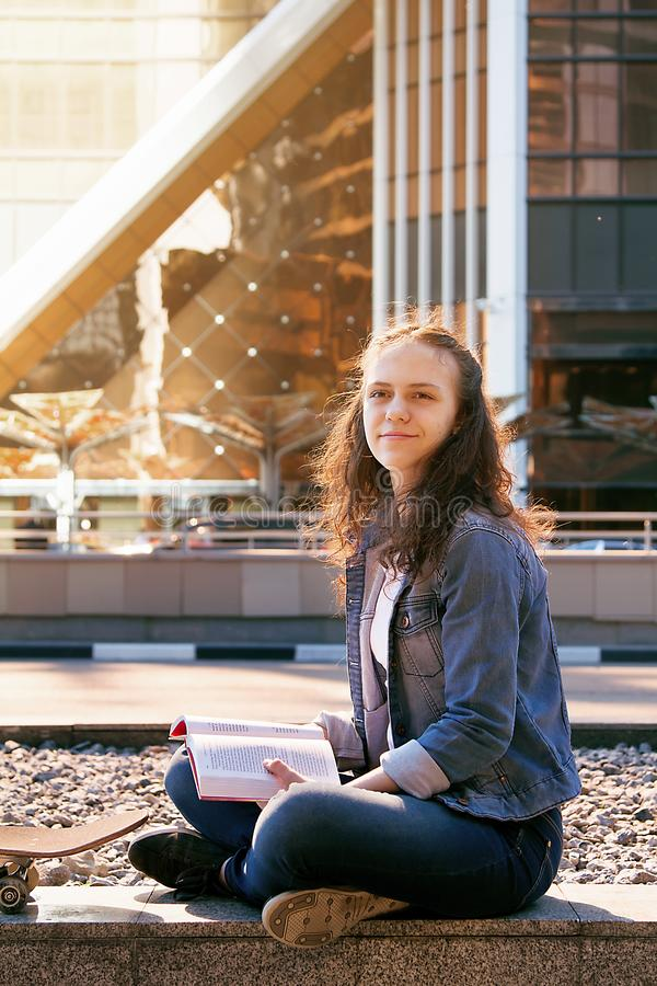 uczennica czyta książkę na ulicie w dużym mieście i marzy obraz stock