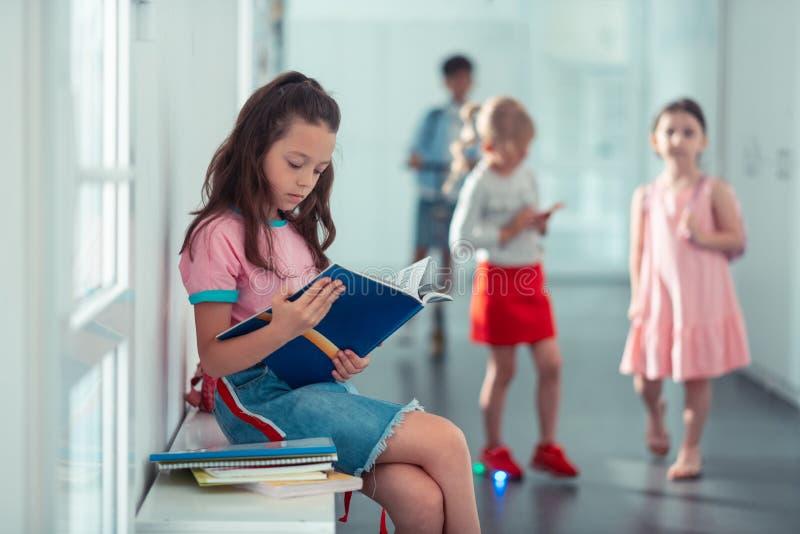 Uczennica jest ubranym drelichu spódnicowego obsiadanie i czytelniczą książkę obraz royalty free