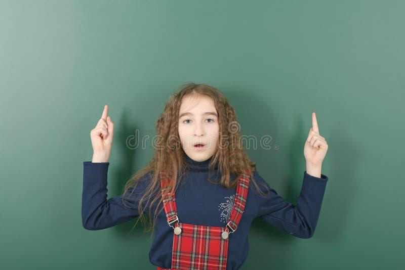 Uczennica pobliski zielony zarząd szkoły Młoda figlarnie dziewczyna pokazuje palec w górę obrazy stock