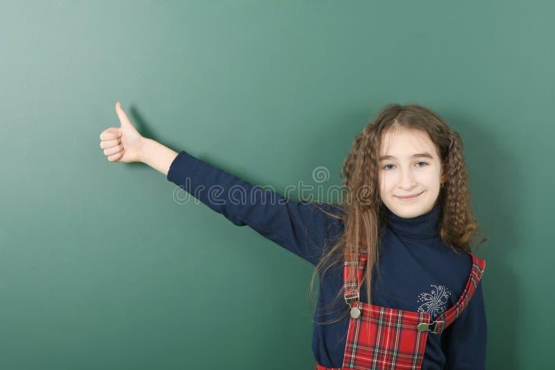 Uczennica pobliski zielony zarząd szkoły Młoda figlarnie dziewczyna pokazuje palec w górę obraz stock