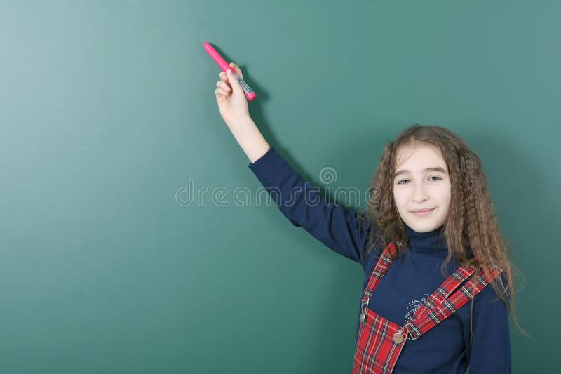 Uczennica pobliski zielony zarząd szkoły Młoda figlarnie dziewczyna trzyma czerwonego pióro w jej ręce fotografia stock