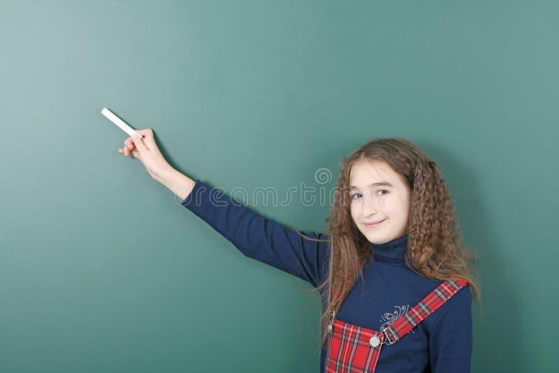 Uczennica pobliski zielony zarząd szkoły Młoda figlarnie dziewczyna trzyma kredę w jego ręce obrazy stock