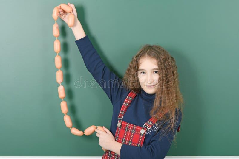Uczennica pobliski zielony zarząd szkoły Młody figlarnie dziewczyna chwyt łańcuch kiełbasy na zielonym zarządzie szkołym obrazy royalty free