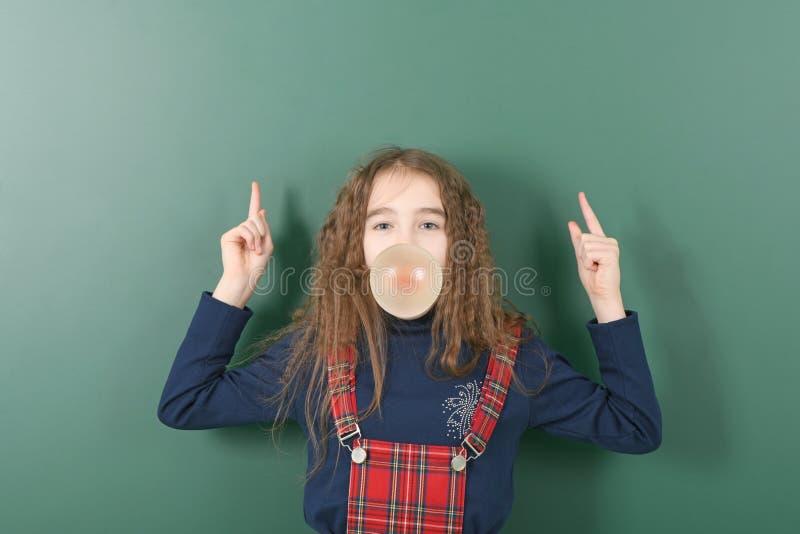 Uczennica pobliski zielony zarz?d szko?y M?oda figlarnie dziewczyna pokazuje palec w g?r? zdjęcie royalty free