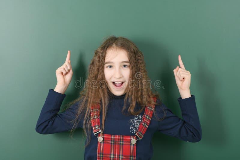 Uczennica pobliski zielony zarz?d szko?y M?oda figlarnie dziewczyna pokazuje palec w g?r? obraz stock