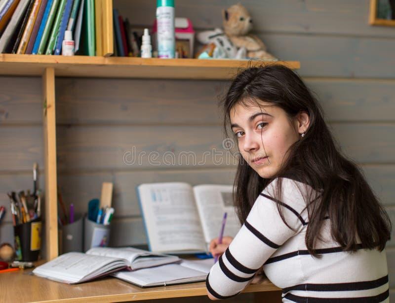 Uczennica robi jego pracie domowej, patrzeje kamerę Edukacja obraz stock