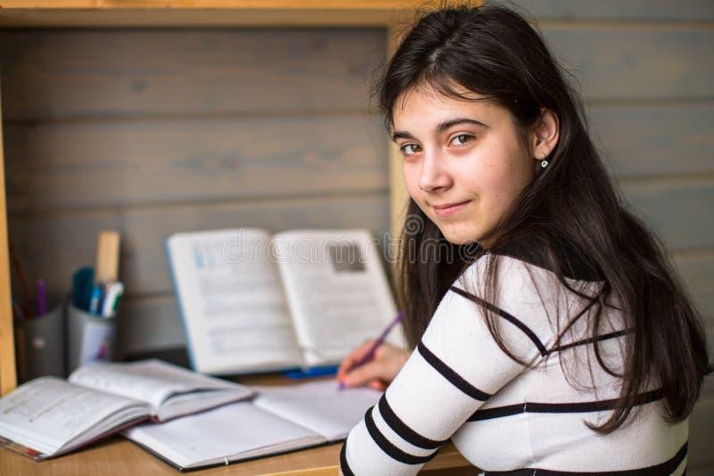 Uczennica robi pracie domowej Patrzeć kamerę Edukacja fotografia stock