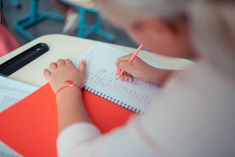 Uczennica robi sumom w jej czerwonym copybook obrazy royalty free
