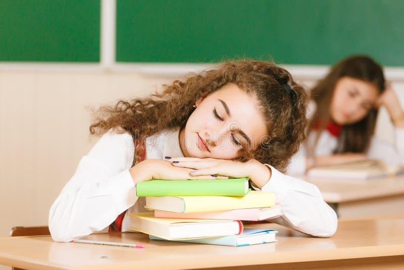 Uczennica spadał uśpiony na książkach przy stołem w sali lekcyjnej fotografia stock