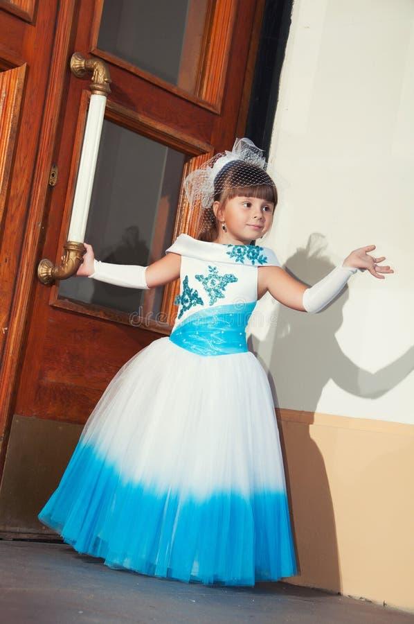 Uczennica w błękitnej i białej mądrze sukni blisko drewnianego drzwi obraz royalty free