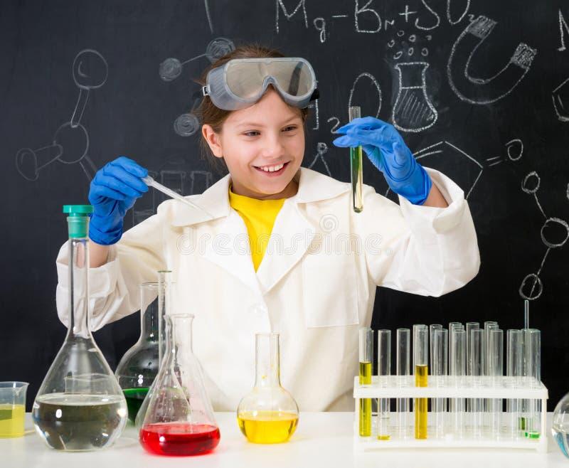Uczennica w białej todze robi eksperymentom z cieczami zdjęcia stock
