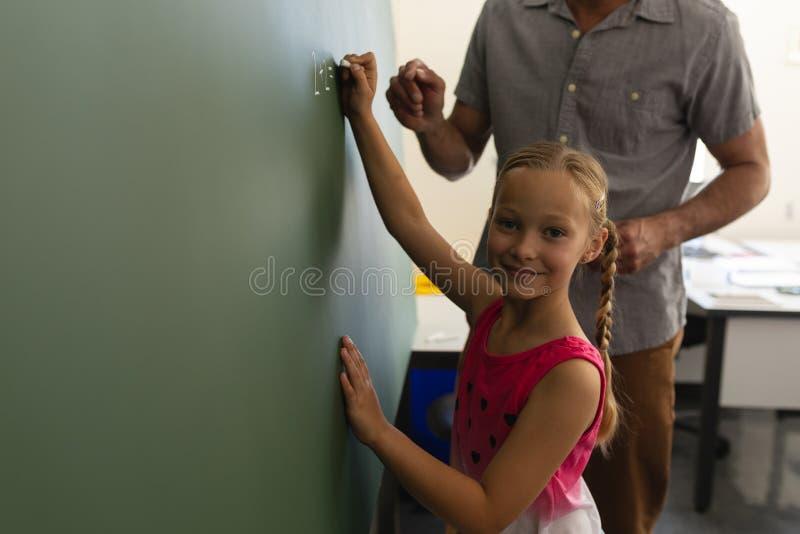 Uczennica z nauczycielem matematykim patrzeje kamerę i pisze na kredowej desce w sali lekcyjnej zdjęcie royalty free