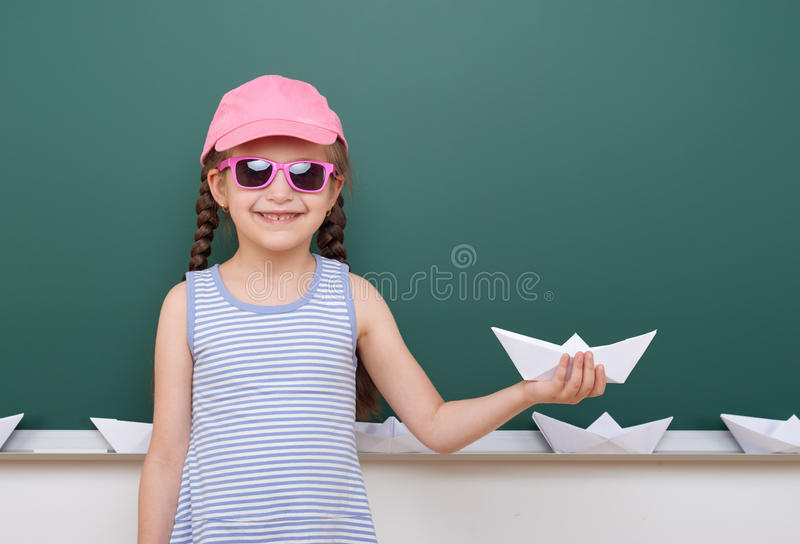 Uczennica z papierową łódkowatą sztuką blisko blackboard, opróżnia przestrzeń, edukaci pojęcie zdjęcia stock