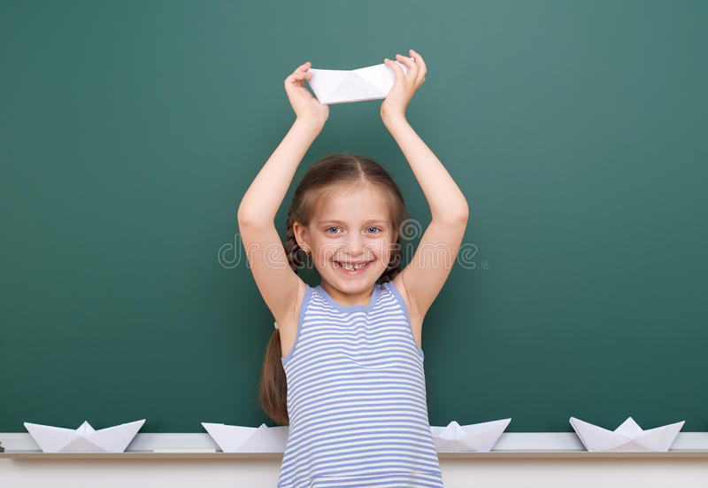 Uczennica z papierową łódkowatą sztuką blisko blackboard, opróżnia przestrzeń, edukaci pojęcie obrazy royalty free