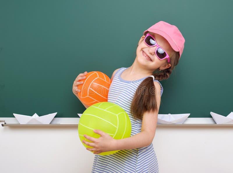 Uczennica z papierową łodzią i balon bawić się blisko blackboard, pusta przestrzeń, edukaci pojęcie zdjęcie stock