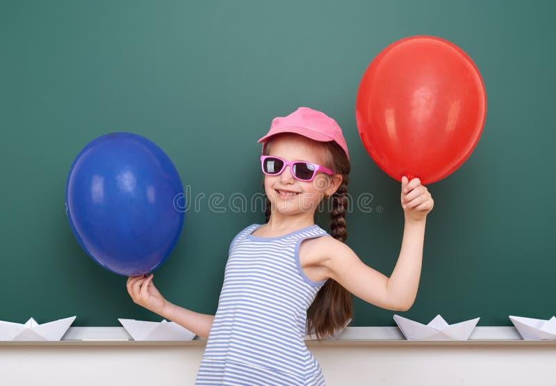 Uczennica z papierową łodzią i balon bawić się blisko blackboard, pusta przestrzeń, edukaci pojęcie obraz stock