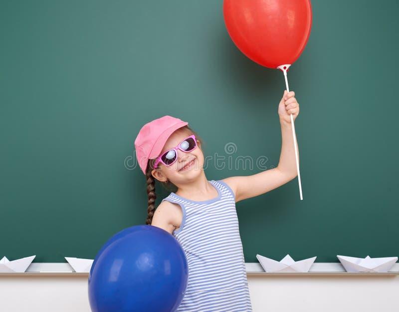 Uczennica z papierową łodzią i balon bawić się blisko blackboard, pusta przestrzeń, edukaci pojęcie obraz royalty free
