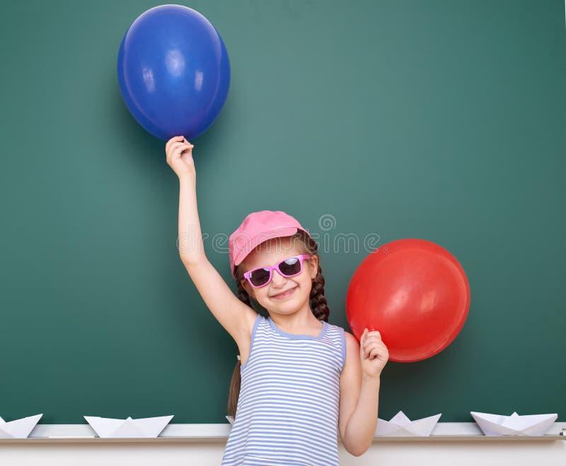 Uczennica z papierową łodzią i balon bawić się blisko blackboard, pusta przestrzeń, edukaci pojęcie fotografia royalty free