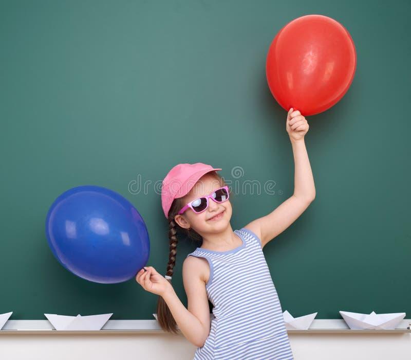 Uczennica z papierową łodzią i balon bawić się blisko blackboard, pusta przestrzeń, edukaci pojęcie obrazy stock