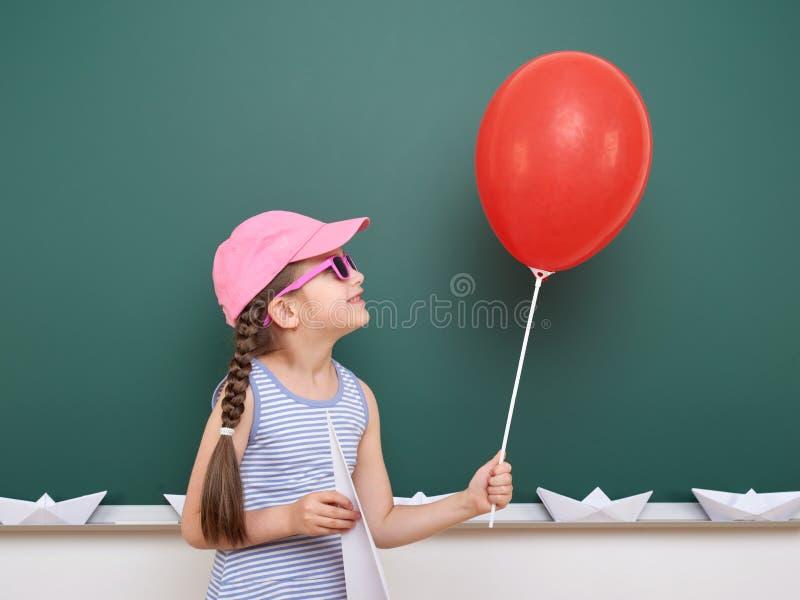 Uczennica z papieru samolotem i balon bawić się blisko blackboard, pusta przestrzeń, edukaci pojęcie obrazy royalty free