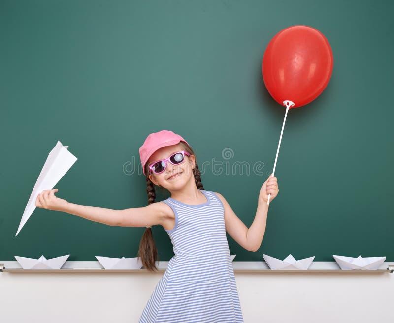 Uczennica z papieru samolotem i balon bawić się blisko blackboard, pusta przestrzeń, edukaci pojęcie zdjęcia stock