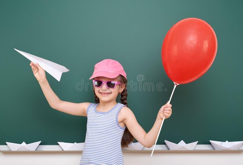 Uczennica z papieru samolotem i balon bawić się blisko blackboard, pusta przestrzeń, edukaci pojęcie obraz royalty free
