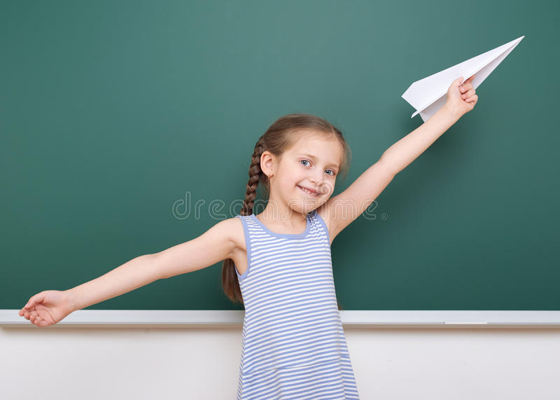 Uczennica z papieru samolotu sztuką blisko blackboard, opróżnia przestrzeń, edukaci pojęcie obraz stock