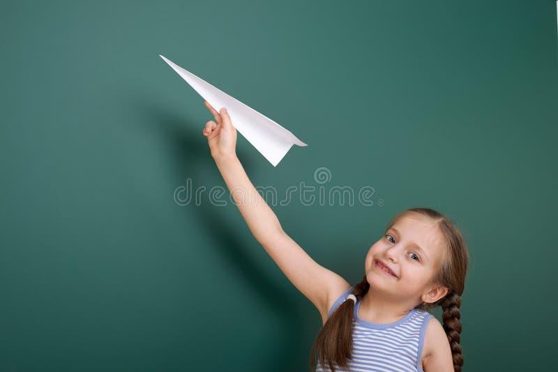 Uczennica z papieru samolotu sztuką blisko blackboard, opróżnia przestrzeń, edukaci pojęcie fotografia royalty free