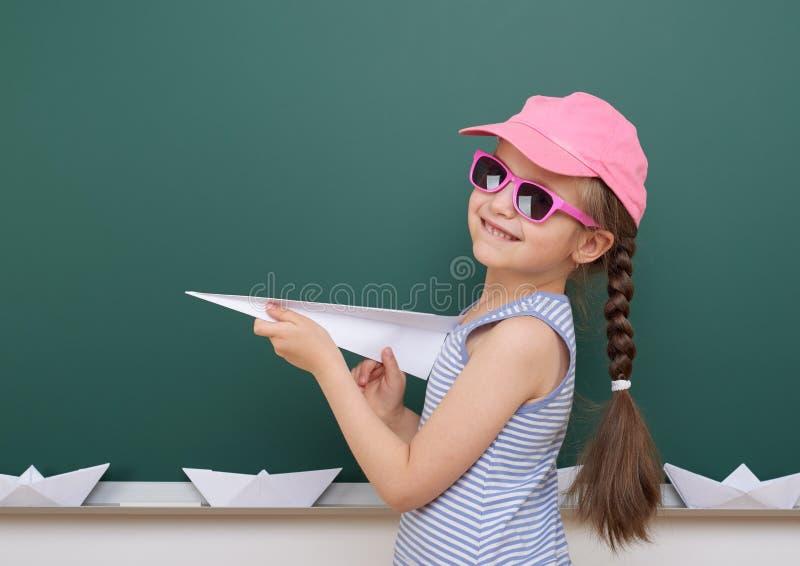 Uczennica z papieru samolotu sztuką blisko blackboard, opróżnia przestrzeń, edukaci pojęcie obrazy stock