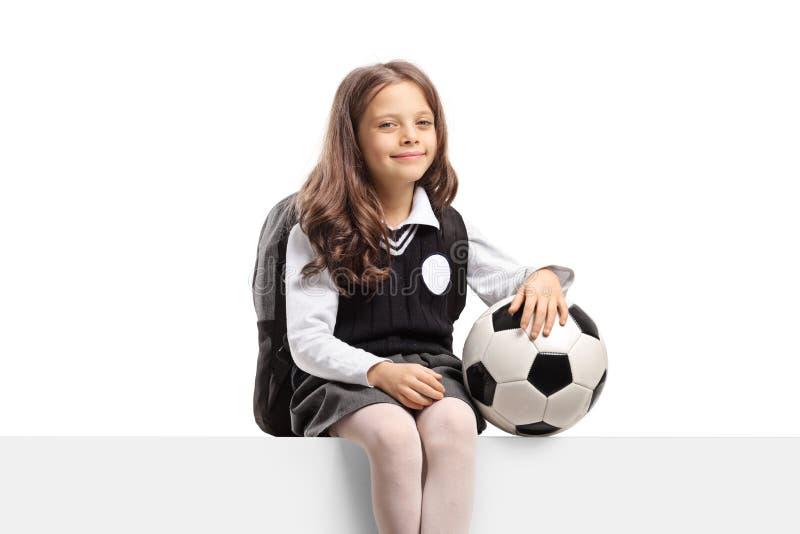 Uczennica z piłki nożnej piłki obsiadaniem na panelu obraz royalty free
