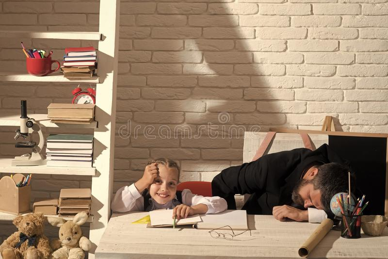Uczennica z szczęśliwą twarzą i jej śpiący tata Nauka pokój i domowy edukaci pojęcie zdjęcie royalty free