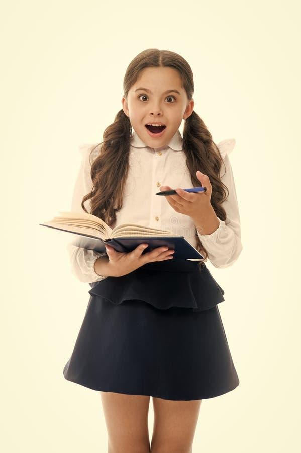 Uczennica z zdziwionym spojrzeniem odizolowywającym na bielu Małe dziecko chwyta książka z piórem tylna szkoły Domowy uczyć kogoś obraz stock