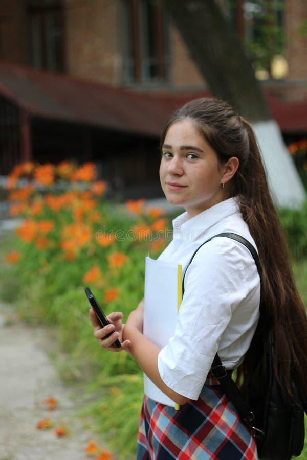 Uczennicy dziewczyna opowiada na telefonie z długie włosy w mundurku szkolnym obraz royalty free
